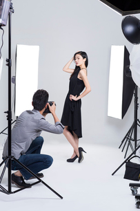 Photographer taking pictures of female model in studioの写真素材 [FYI02217073]