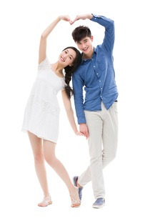 Young couple making heart shape with their armsの写真素材 [FYI02217104]