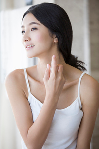 Young woman spraying perfume on her neckの写真素材 [FYI02217157]
