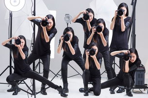 Multiple images of photographer taking picture in studioの写真素材 [FYI02217226]