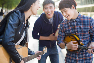 Young adults playing musical equipment on streetの写真素材 [FYI02217247]