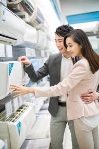 Young couple buying air conditioner in electronics storeの写真素材 [FYI02217348]