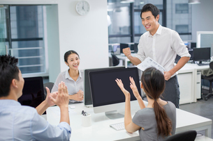 Young business people cheering in officeの写真素材 [FYI02217378]