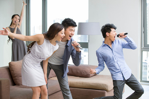 Happy young friends singing and dancing in living roomの写真素材 [FYI02217387]
