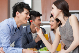 Young woman feeding boyfriend tomatoの写真素材 [FYI02217431]