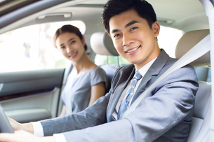 Young businessman driving car with his wife sitting next to himの写真素材 [FYI02217453]