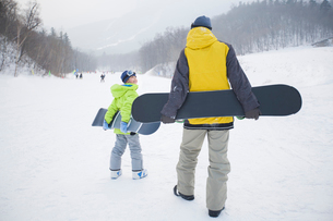Young father and son walking with snowboards on the snowの写真素材 [FYI02217473]