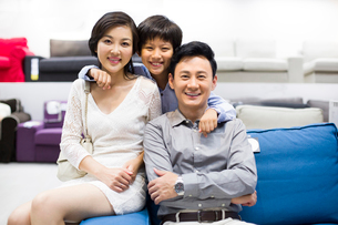 Cheerful family sitting in couch in furniture shopの写真素材 [FYI02217510]