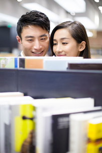 Young couple choosing books in bookstoreの写真素材 [FYI02217521]