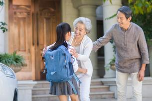 Schoolgirl running into grandmother's armsの写真素材 [FYI02217535]