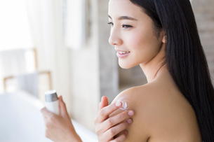 Young woman applying moisturizer to shoulderの写真素材 [FYI02217618]