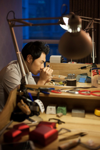 Male jeweler examining a diamond with loupeの写真素材 [FYI02217654]