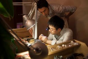 Male jeweler examining jewelry with loupeの写真素材 [FYI02217662]