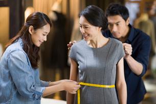 Fashion designers taking measurement of customerの写真素材 [FYI02217709]
