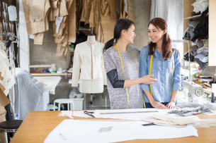 Two female fashion designers talking in studioの写真素材 [FYI02217736]