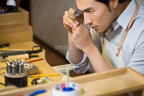 Male jeweler examining a diamond with loupeの写真素材 [FYI02217739]