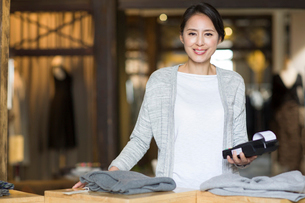 Clothing store owner with credit card readerの写真素材 [FYI02217760]