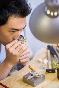 Male jeweler examining a diamond with loupeの写真素材 [FYI02217767]