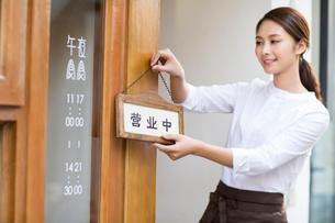 Young waitress with open sign in restaurant doorwayの写真素材 [FYI02217789]