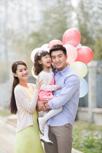 Happy young family with balloonsの写真素材 [FYI02217797]
