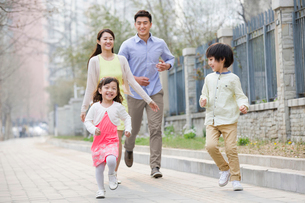 Happy young family runningの写真素材 [FYI02217817]