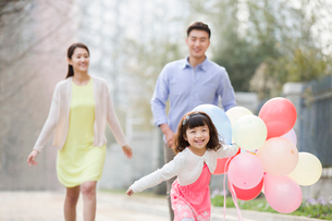 Happy young family running with balloonsの写真素材 [FYI02217829]