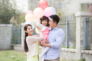 Happy young family with balloonsの写真素材 [FYI02217847]