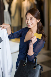 Young woman with credit card in clothing storeの写真素材 [FYI02217893]
