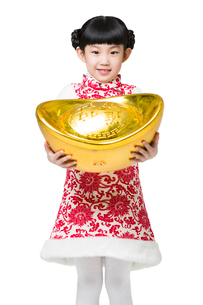 Happy girl holding a large Chinese traditional currency yuanbaoの写真素材 [FYI02217922]