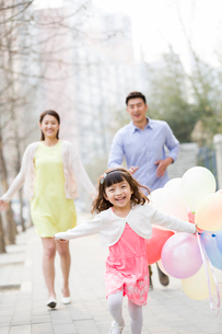 Happy young family running with balloonsの写真素材 [FYI02217924]