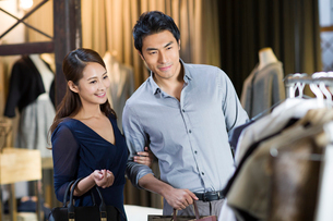 Young couple choosing dress in clothing storeの写真素材 [FYI02217953]