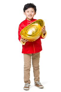 Happy boy holding a large Chinese traditional currency yuanbaoの写真素材 [FYI02218002]