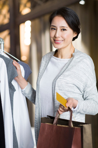 Mature woman with credit card in clothing storeの写真素材 [FYI02218007]