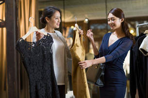 Clothing store owner helping customer with choosing dressの写真素材 [FYI02218011]