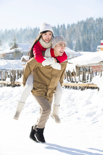 Young man giving his girlfriend piggyback in the snowの写真素材 [FYI02218030]