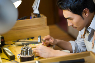 Male jeweler working in studioの写真素材 [FYI02218042]