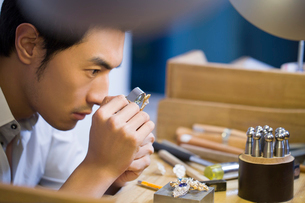 Male jeweler examining a diamond with loupeの写真素材 [FYI02218072]