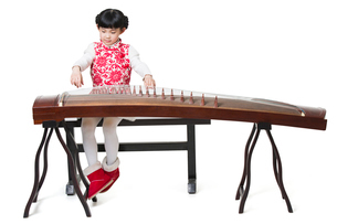 Happy girl playing traditional Chinese zitherの写真素材 [FYI02218191]