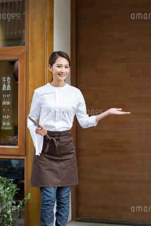 Young waitress greeting in restaurant doorwayの写真素材 [FYI02218220]