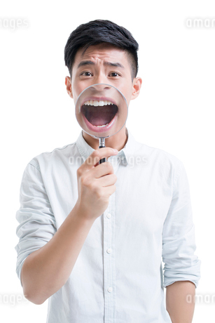 Young man holding a magnifying glass in front of his mouthの写真素材 [FYI02218541]