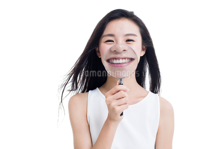 Young woman holding a magnifying glass in front of her mouthの写真素材 [FYI02218604]