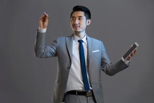Happy young businessman using digital tabletの写真素材 [FYI02218616]