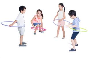 Happy children spinning plastic hoopsの写真素材 [FYI02218630]