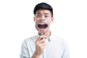 Young man holding a magnifying glass in front of his mouthの写真素材 [FYI02218674]