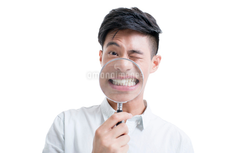Young man holding a magnifying glass in front of his mouthの写真素材 [FYI02218684]