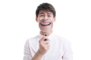 Young man holding a magnifying glass in front of his mouthの写真素材 [FYI02218693]