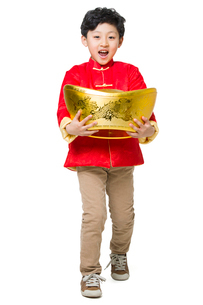 Happy boy holding a large Chinese traditional currency yuanbaoの写真素材 [FYI02218995]