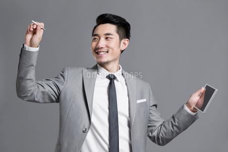 Happy young businessman using digital tabletの写真素材 [FYI02219197]