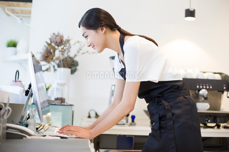 Coffee shop owner using computerの写真素材 [FYI02219325]