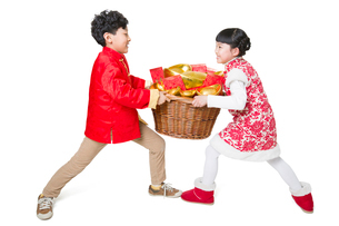 Happy children carrying red envelopes and Chinese traditional currency yuanbaoの写真素材 [FYI02219438]